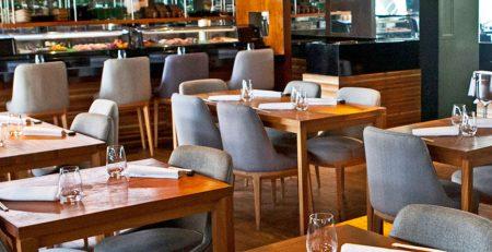 Fotografía de un conjunto de muebles para bar y cafetería compuesto por sillas y mesas de madera